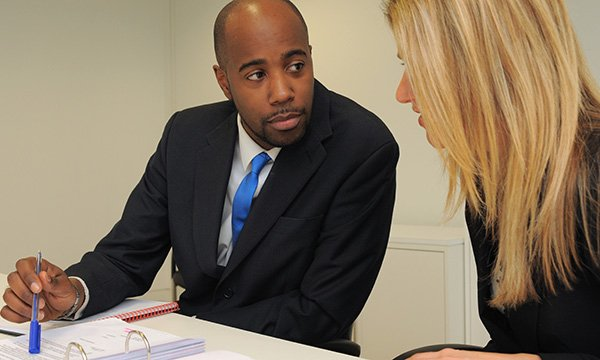 Man and woman sit in formal setting looking over a file of paperwork