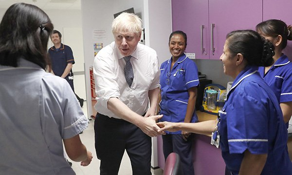 Prime Minister Boris Johnson speaking to nurses during a visit to the East Midlands and East of England Genomic Laboratory Hub at Addenbrooke's Hospital in Cambridge in October 2019, before the government promised to boost NHS nursing numbers by 50,000
