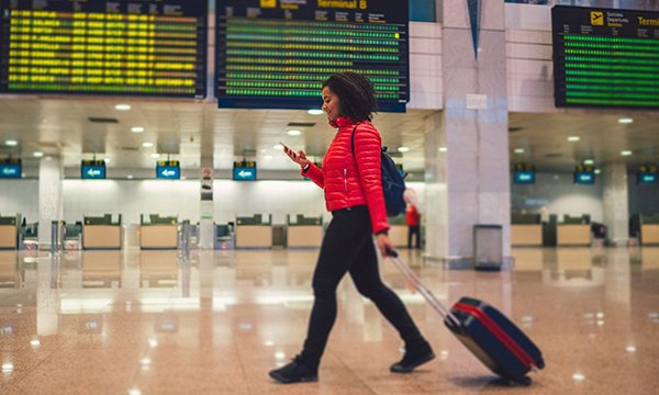 Picture shows a young woman with a suitcase at an airport. The Royal College of Emergency Medicine wants nationally coordinated  programme to recruit emergency nurses from overseas.