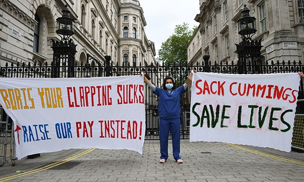 nurse protests outside the gates to Downing Street about pay and PPE
