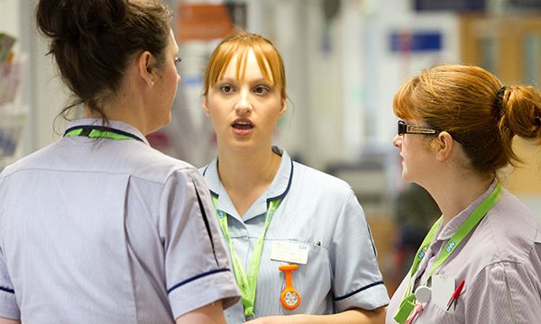 Picture shows nurses in conversation on an NHS hospital ward