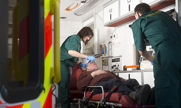 Picture shows an older man in an ambulance being treated by paramedics