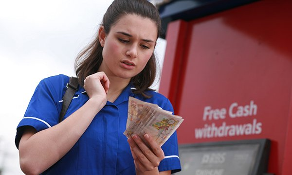 in nurse's uniform frowning as she counts money at a cash machine