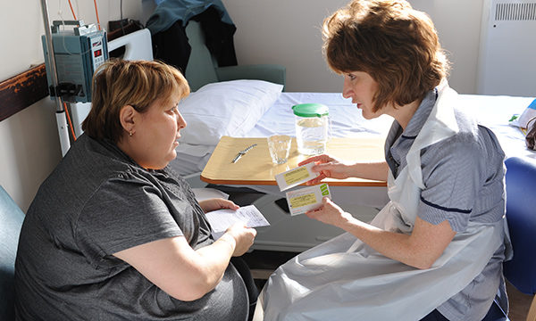 Female nurse talking to a patient about their medication