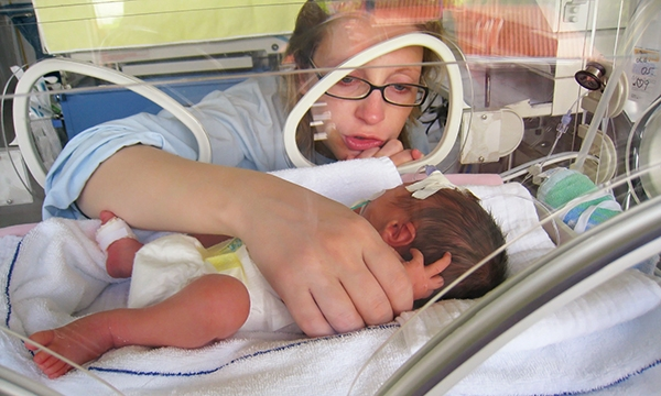 Woman with baby in baby incubator