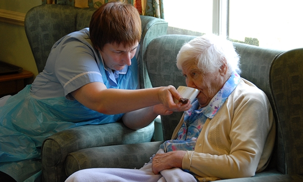care home staff member helps resident drink