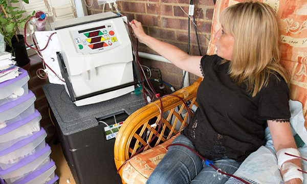 woman uses home dialysis machine