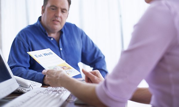 obese man consults clinician who is holding an 'eat well' leaflet