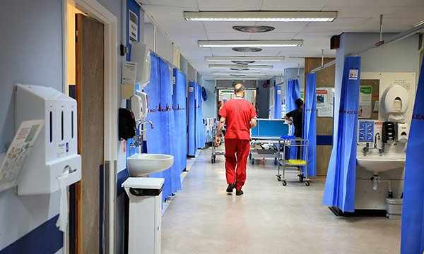 Nurse walking down a hospital ward corridor
