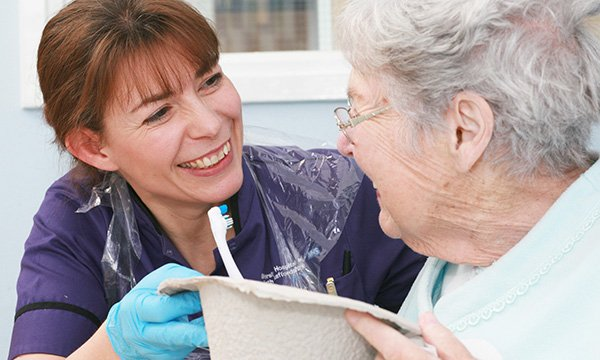 A nurse helps an elderly lady clean her teeth. Picture: Neil O'Connor