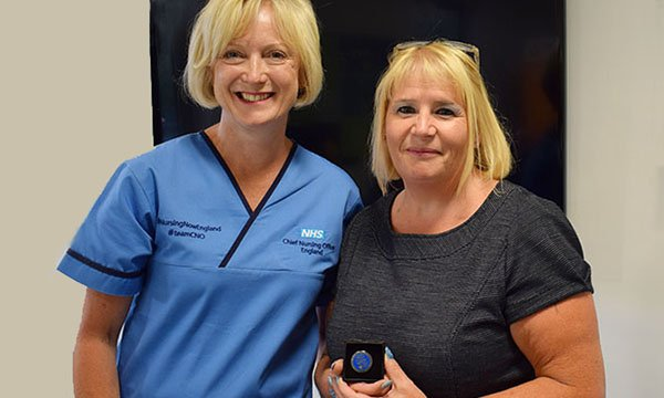 Mental health lead Gill Drummond (right) receives the CNO Silver Award for Excellence in Nursing from chief nursing officer for England Ruth May