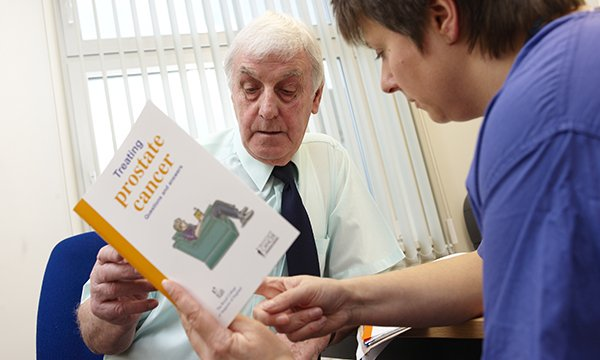 Picture shows an older man being handed a booklet on prostate cancer by a nurse. The prostate cancer specialist nursing workforce could collapse within the next decade unless urgent action is taken, according to researchers.