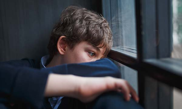 Picture shows a model depicting a depressed teenage boy sitting by a window. Learning disability and autism significantly increase the chances of having a mental health condition and are also predictive of poorer general health, a study shows.
