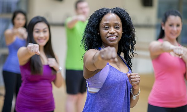 Women smiling in a fitness class. Maintaining your own wellbeing is hard when you're a nurse, but important