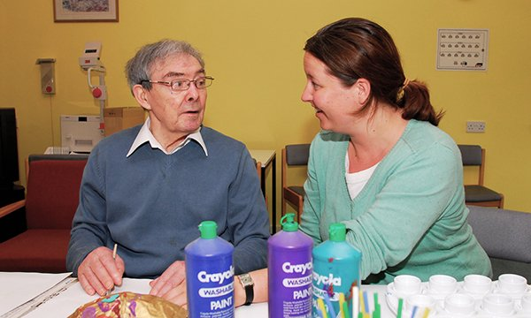 A nurse sits talking to a nursing home resident as he undertakes a craft activity