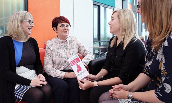 women discussing menopause in the workplace, using an information leaflet to help them