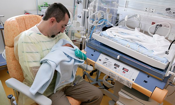 Picture shows a father holding a baby in a neonatal unit. This editorial says parents need more support when infants go into neonatal care, but proposals in the latest consultation fall short.