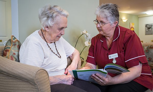 Picture shows a care home supervisor talking to a resident. Healthcare professionals can help meet the needs of older people approaching the end of life by asking the right questions.