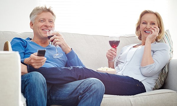 man and woman snuggle on sofa, smiling and drinking wine