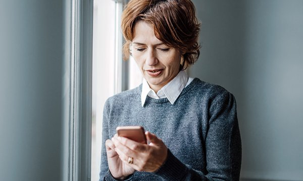 woman stands by window reading her phone
