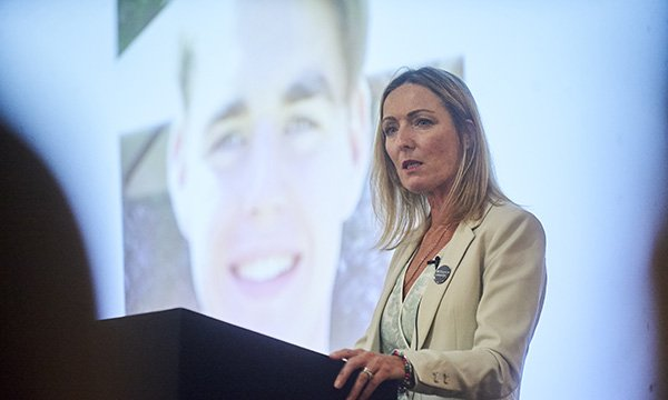 Image show campaigner Paula McGowan speaking at a conference with an image of her son Oliver behind her