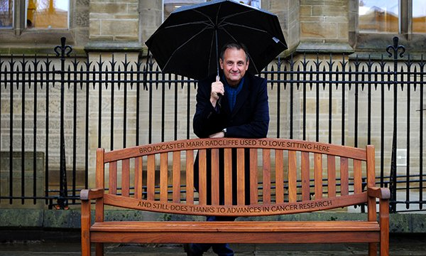 Picture shows broadcaster Mark Radcliffe standing next to a park bench in the grounds of the University of Manchester which bears his tribute to cancer research.