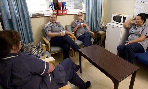 Nurses sit in a staff room chatting over coffee