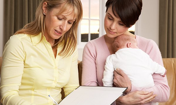 Picture shows a health visitor with a mother and baby. Health visitor numbers in England are the lowest on record, according to an analysis of NHS data by the Labour Party.