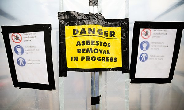 Yellow safety signs reads: 'Danger – Asbestos removal in progress