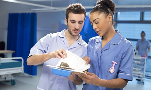 two nurses confer on a ward