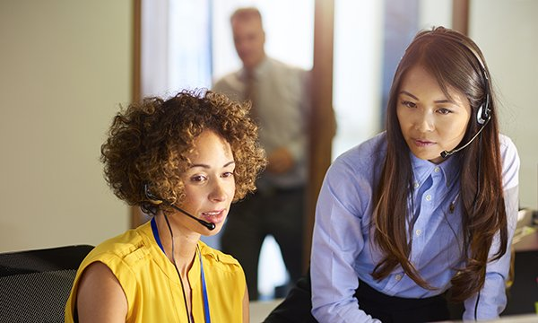 Picture shows two women wearing headsets, and one of them is speaking to a caller. Nurse specialists at Prostate Cancer UK receive detailed training including mentors and a learning contract to equip them to deal with requests for help and advice.