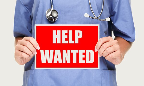 nurse's hands hold up sign saying 'help wanted'