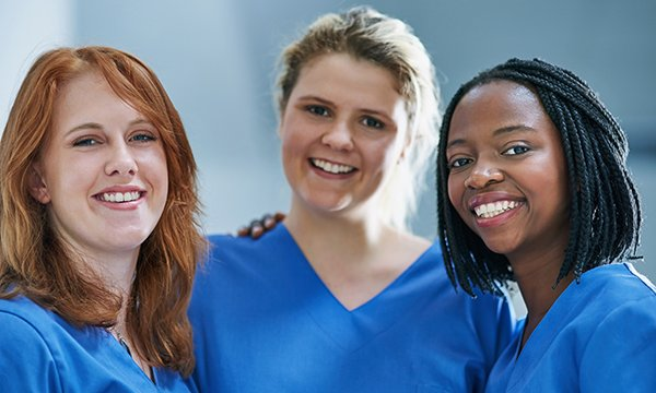 Three nurses stand together, smiling