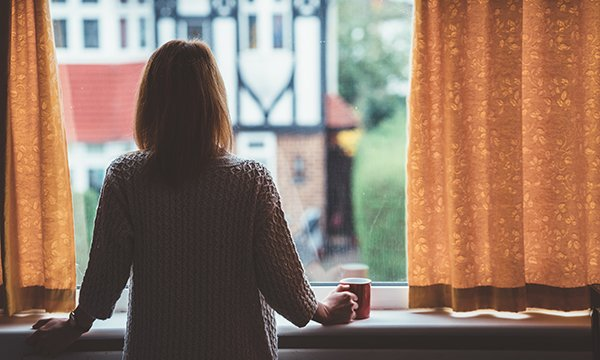 A woman standing alone at a window, looking outside. People who have had close, sustained contact with a person confirmed to have coronavirus are being told to self-isolate for 14 days
