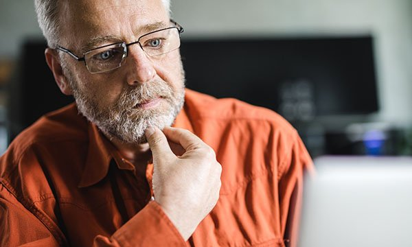 Picture shows an older man appearing anxious while looking at a computer screen. Research by Macmillan shows thousands of people with cancer are left anxious, depressed or confused after finding misleading information online.