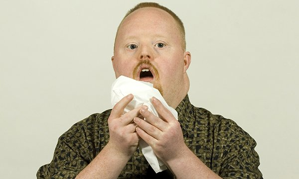 Image shows learning disability servicer user sneezing in to a tissue