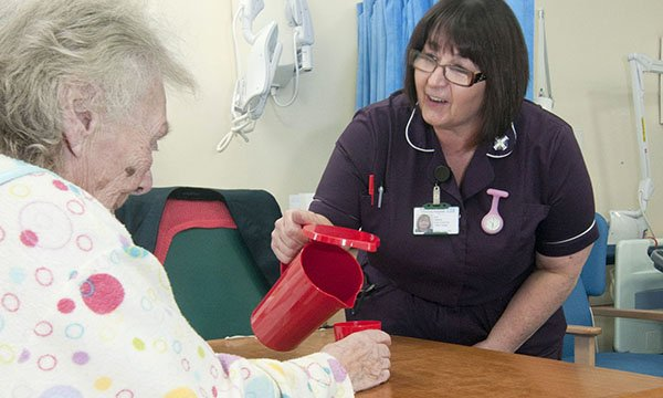 Nurse attending to an older patient who is experiencing and needs hydration