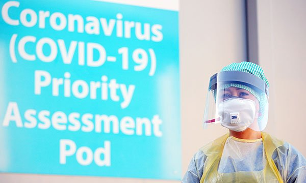 A woman stands next to a sign about coronavirus wearing PPE, including a face mask. Picture: Shutterstock