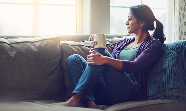 woman sits on sofa, mug in hand, looking out of a window