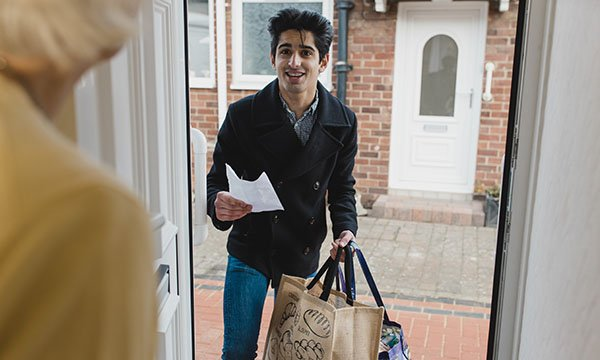 Image shows a young man bringing some shopping to his vulnerable neighbour during the COVID-19 pandemic