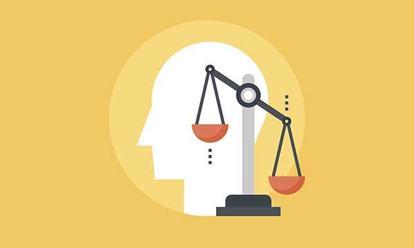Vector illustration of scales of justice against background of profile of human head. The article says mental health nurses must safeguard the vulnerable if powers in Coronavirus Act 2020 are activated.