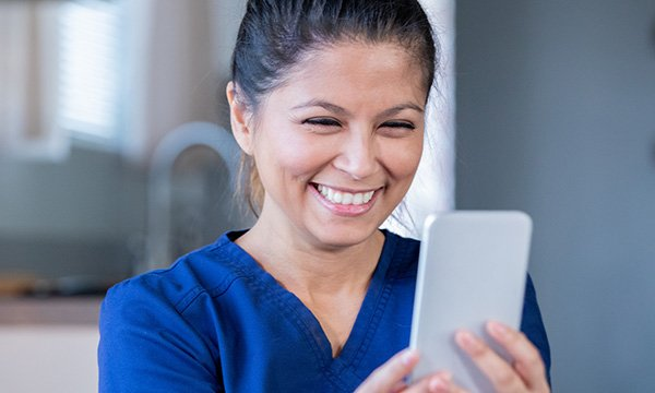 nurse smiles as she looks at her phone