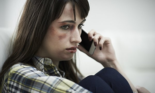 woman with bruised face looks sad as she makes a phone call