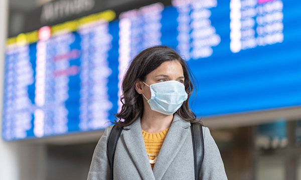 Picture shows a woman wearing a face mask, with an airport departures board in the background