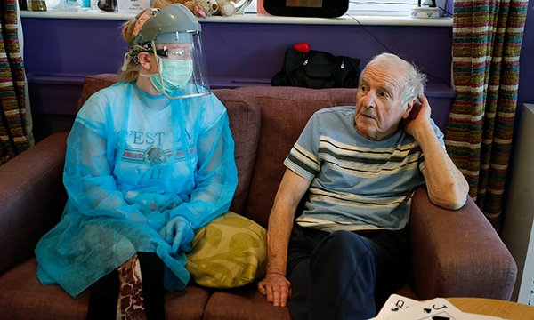 Image of a care home nurse wearing personal protective equipment whilst attending to a resident