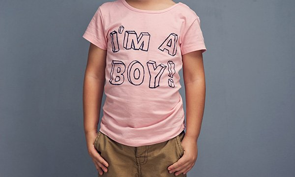 Picture shows a child wearing a pink T-shirt with 'I'm a boy!' printed on it