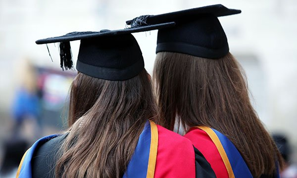 Two women dressed in mortar board and gowns for their graduation – as 2,000 nursing students face long delay to graduate as a result of the pandemic