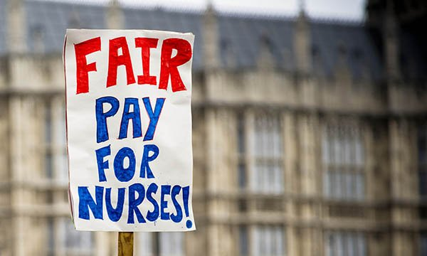 Picture shows a placard demanding fair pay for nurses, with houses of parliament in the background