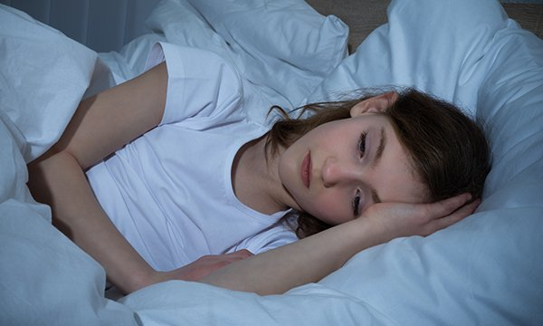 Picture sows a young girl with her head on a pillow, touching her head with her hand and looking sad