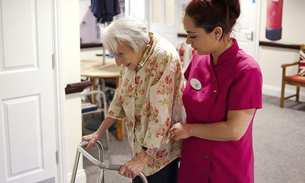 Picture shows a carer helping an older woman who is walking with the help of a zimmer frame